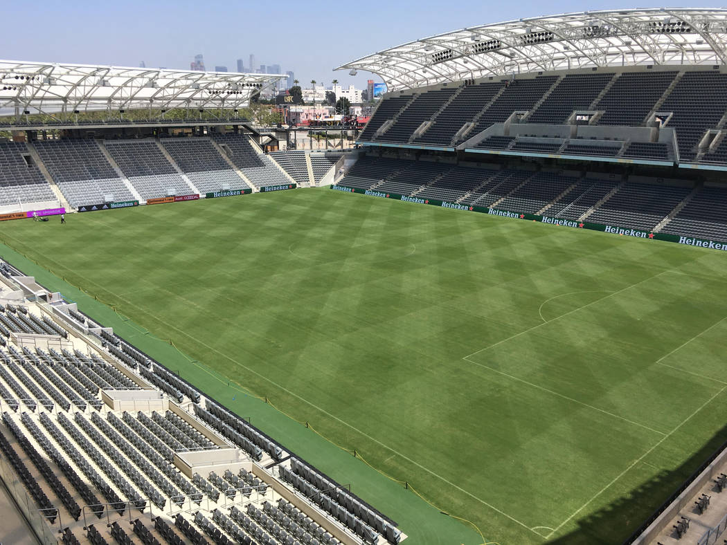 In this Thursday, April 26, 2018, photo workers prepare the playing field at Banc of California ...