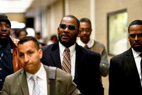 Musician R. Kelly, center, leaves the Daley Center after a hearing in his child support case, M ...