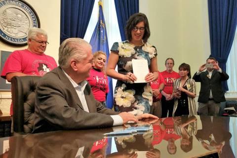 State Sen. Yvanna Cancela, D-Las Vegas, center, holds Senate Bill 262, which will require drug ...