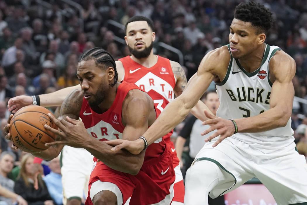 Milwaukee Bucks' Giannis Antetokounmpo and Toronto Raptors' Kawhi Leonard go after a loose ball ...