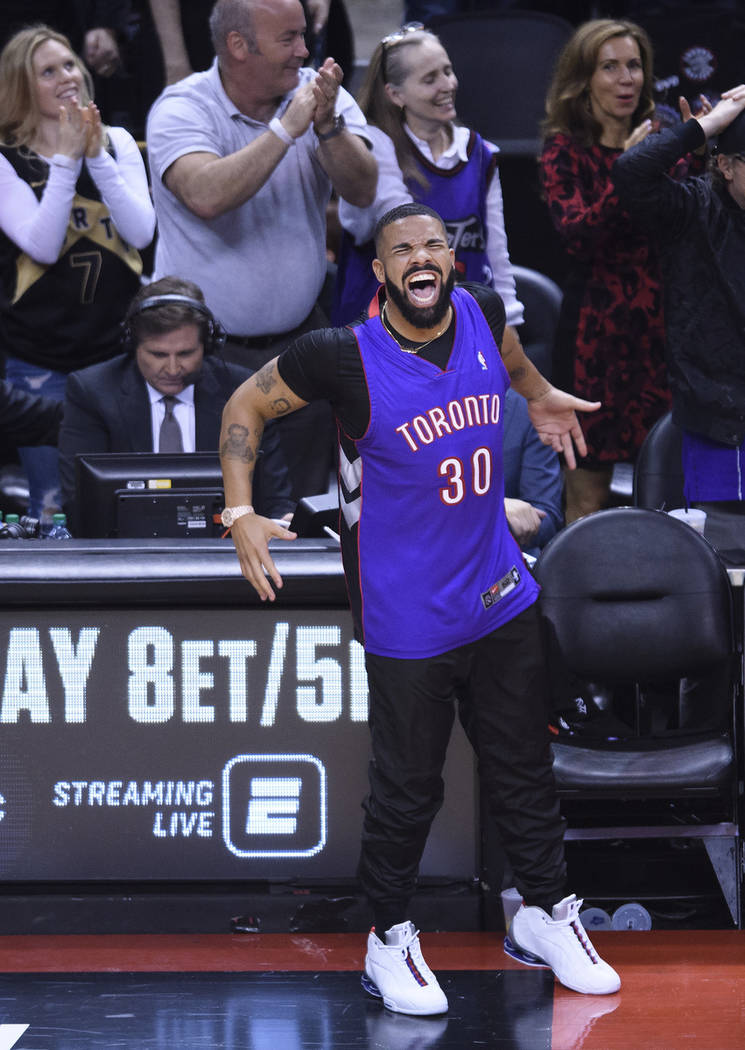 Rapper Drake reacts courtside as the Toronto Raptors play the Golden State Warriors during the ...