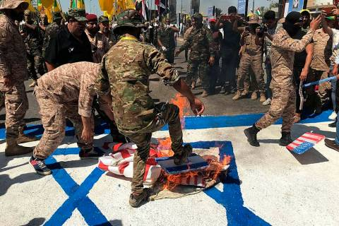 "Iraqi Popular Mobilization Forces burn representations of U.S. and Israeli flags during ""a ..."
