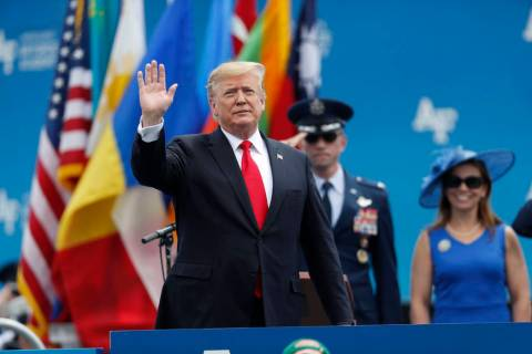 President Donald Trump waves as he takes the stage to speak at the U.S. Air Force Academy gradu ...
