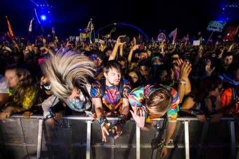 Attendees headbang as Excision performs at the Kinetic Field stage during the first day of the ...
