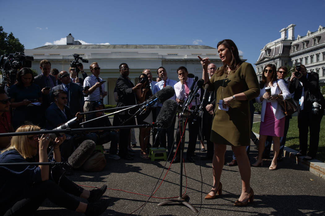 White House press secretary Sarah Sanders talks to reporters outside the White House, Friday, M ...