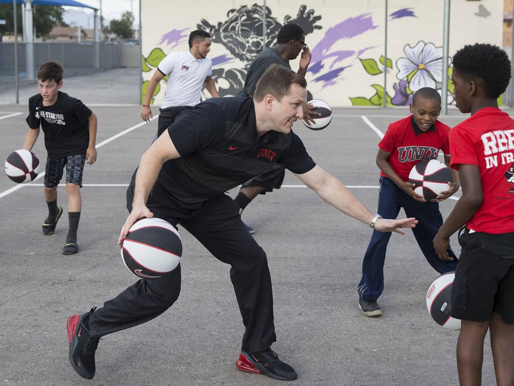 UNLV head basketball coach T.J. Otzelberger, center, dribbles through a crowd of kids during a ...