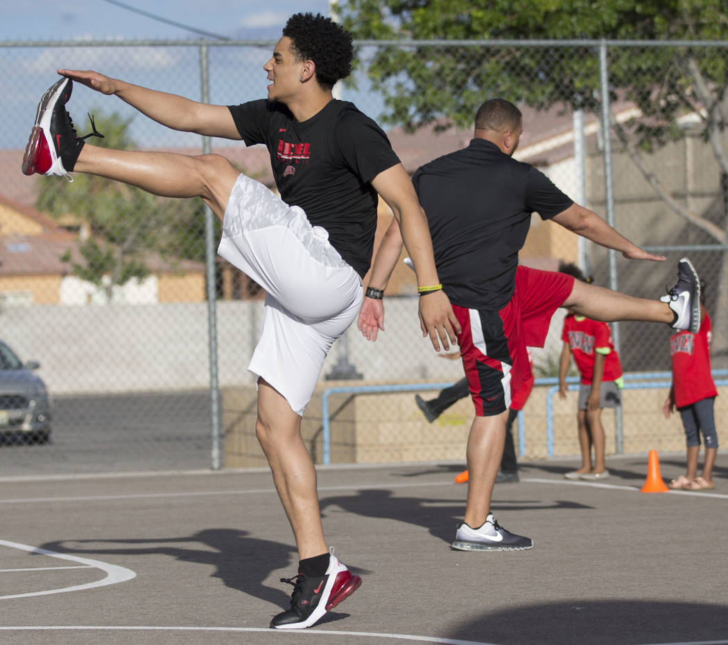 UNLV player Marvin Coleman II, left, demonstrates a stretch during a youth clinic hosted by UNL ...