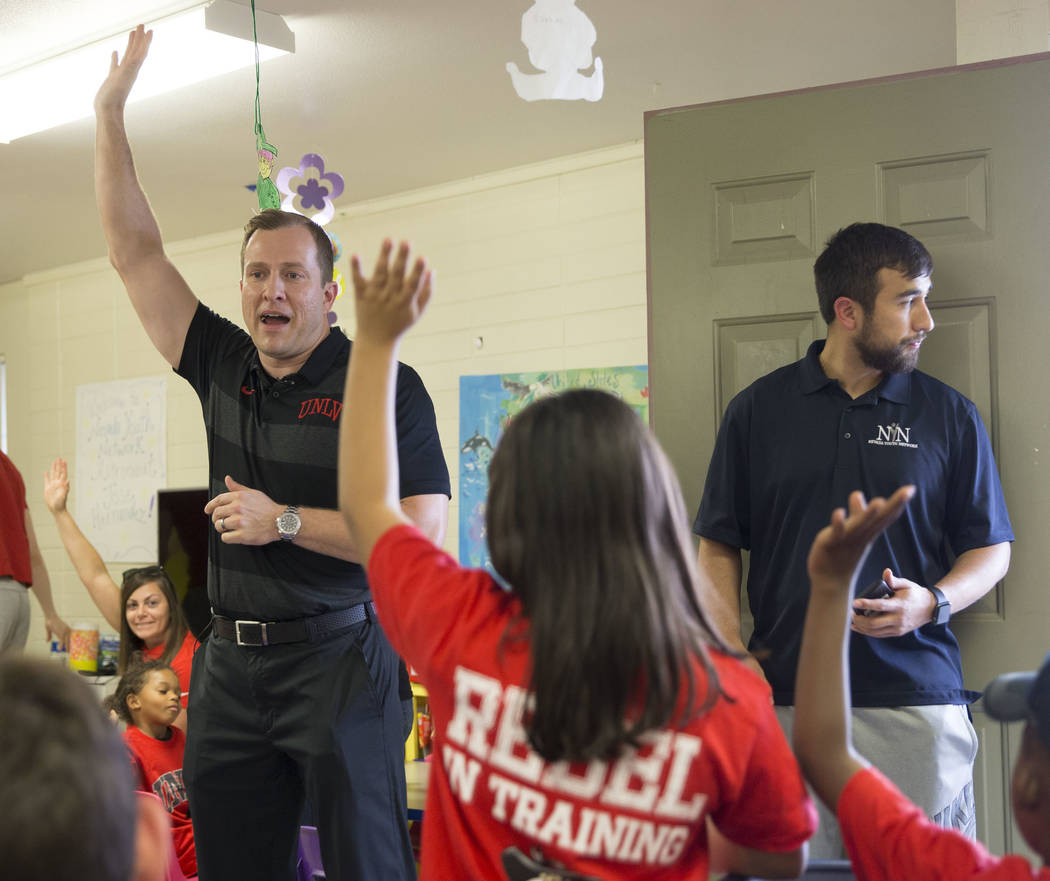 UNLV head basketball coach T.J. Otzelberger, left, answers questions from children during a you ...