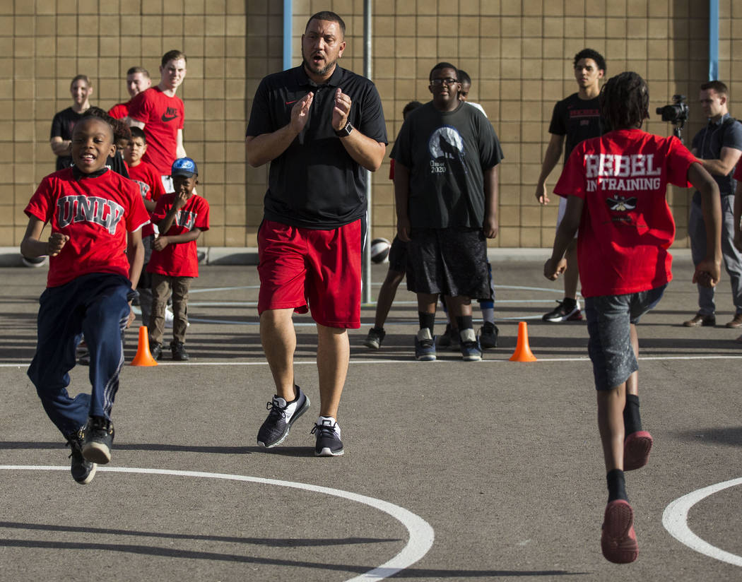 UNLV assistant coach DeShawn Henry, center, cheers on kids with the Nevada Youth Network during ...