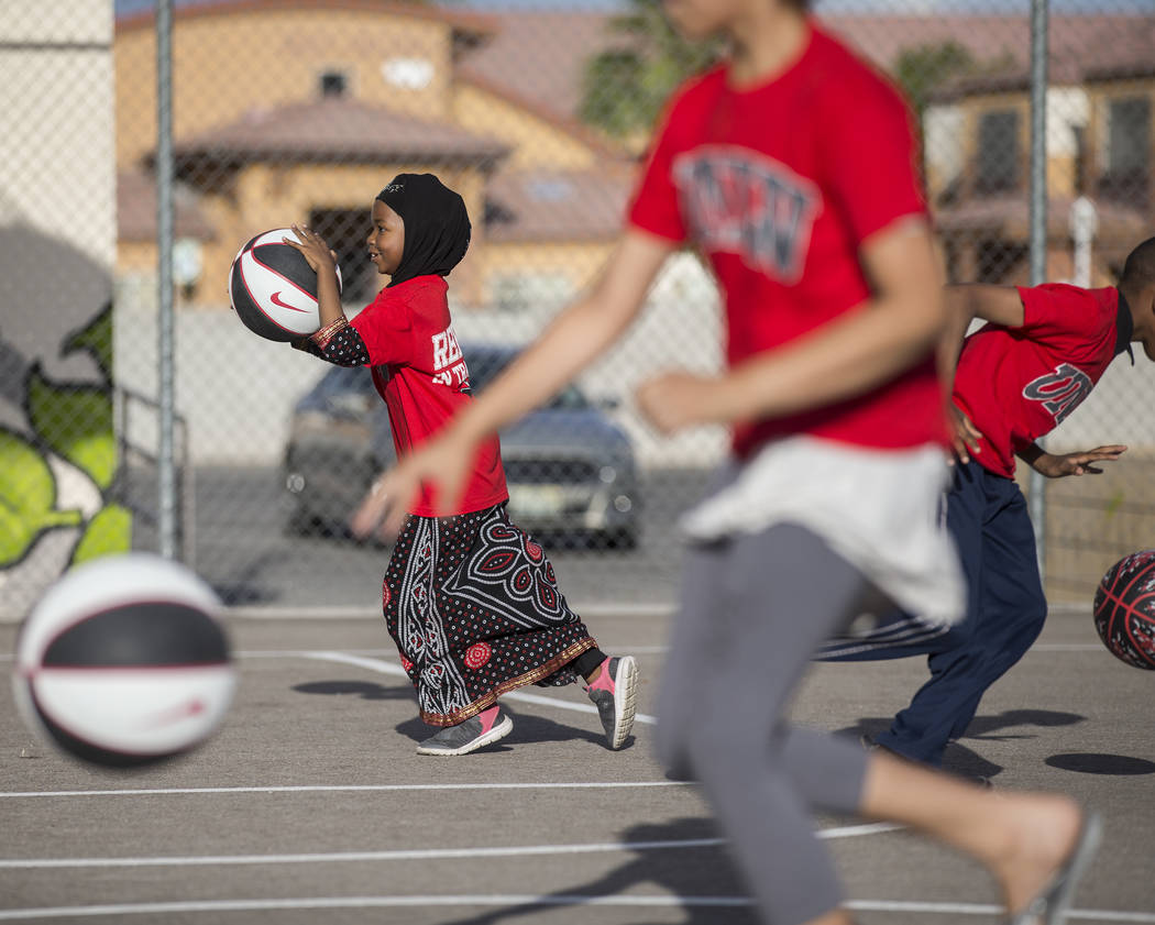 Fardosa Blial, left, 6, dribbles a basketball during a youth clinic hosted by UNLV head basketb ...