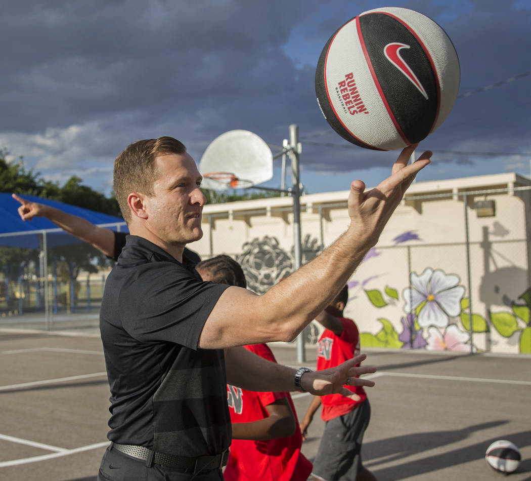 UNLV head basketball coach T.J. Otzelberger spins a basketball on his finger during a youth cli ...