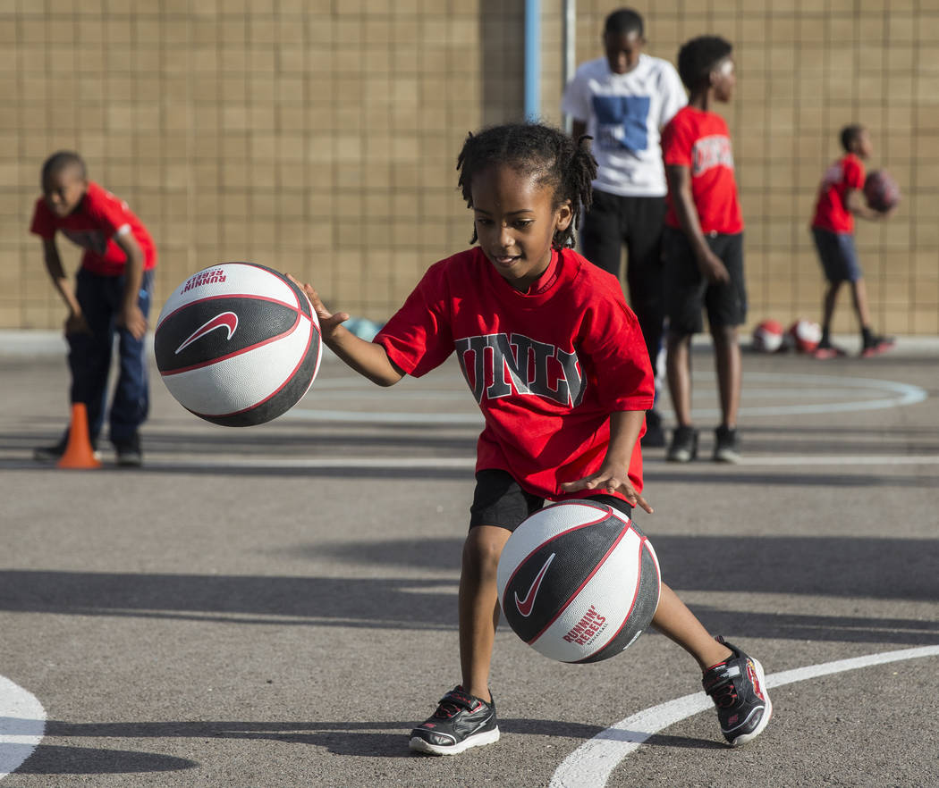 Jayceon Jackson, 6, practices dribbling two basketballs during a youth clinic hosted by UNLV he ...