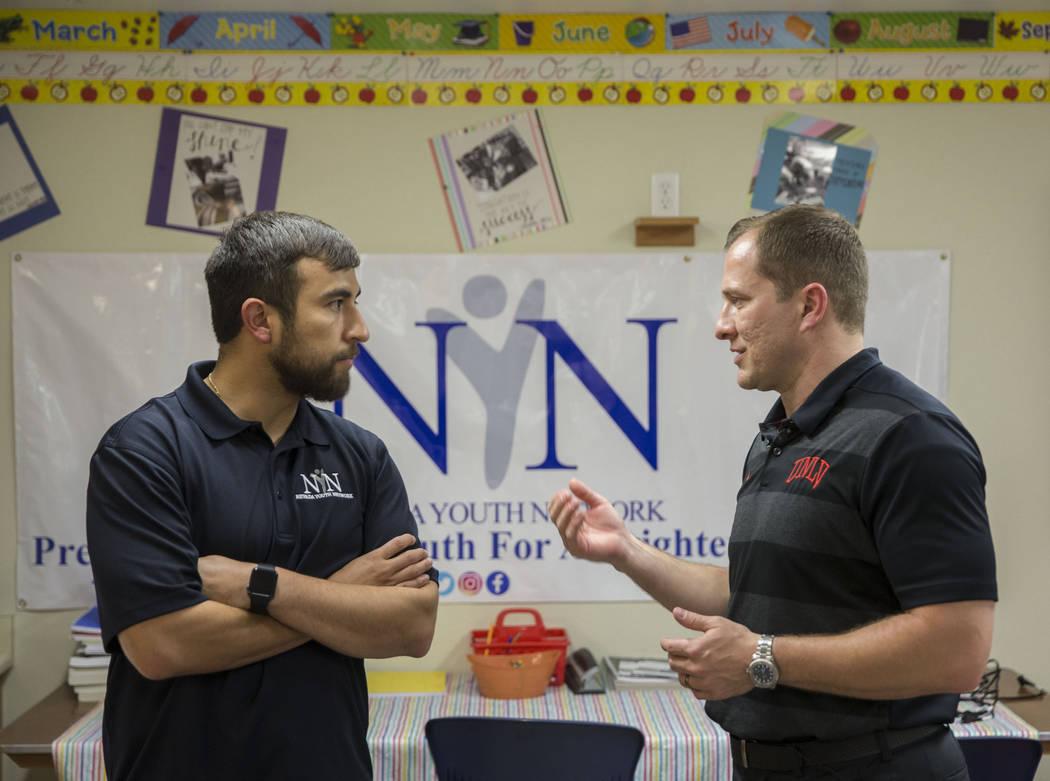 UNLV head basketball coach T.J. Otzelberger, right, speaks with Nevada Youth Network founder Mi ...