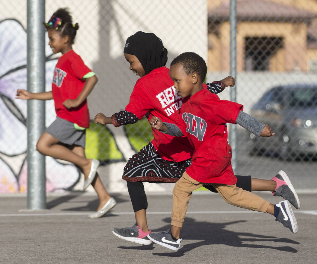 Fardosa Blial, center, 6, races Ryan Fraley, right, 4, during a youth clinic hosted by UNLV hea ...