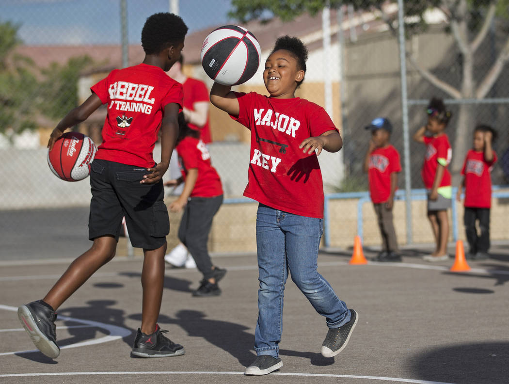 Kids with the Nevada Youth Network practice dribbling during a youth clinic hosted by UNLV head ...
