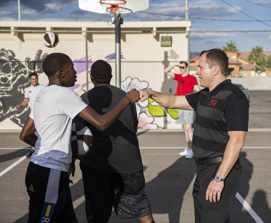 UNLV head basketball coach T.J. Otzelberger, right, pounds it out with Isaiah Taylor during a y ...
