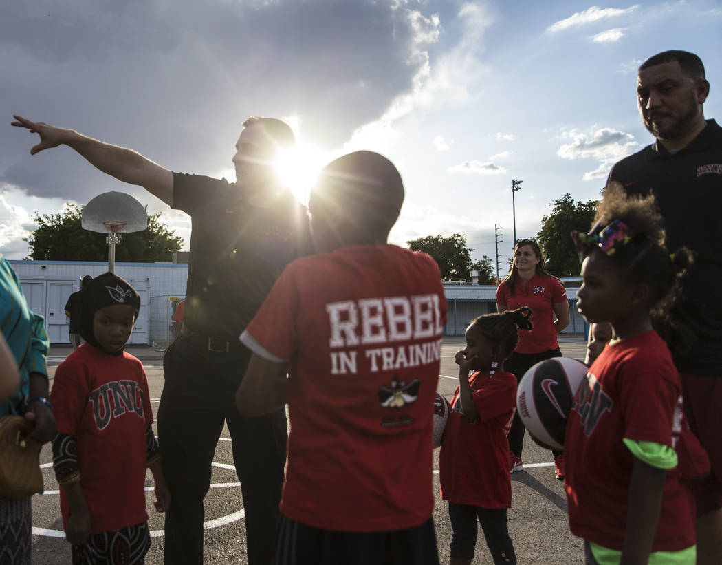 UNLV head basketball coach T.J. Otzelberger, top/left, directs kids during a youth clinic at th ...