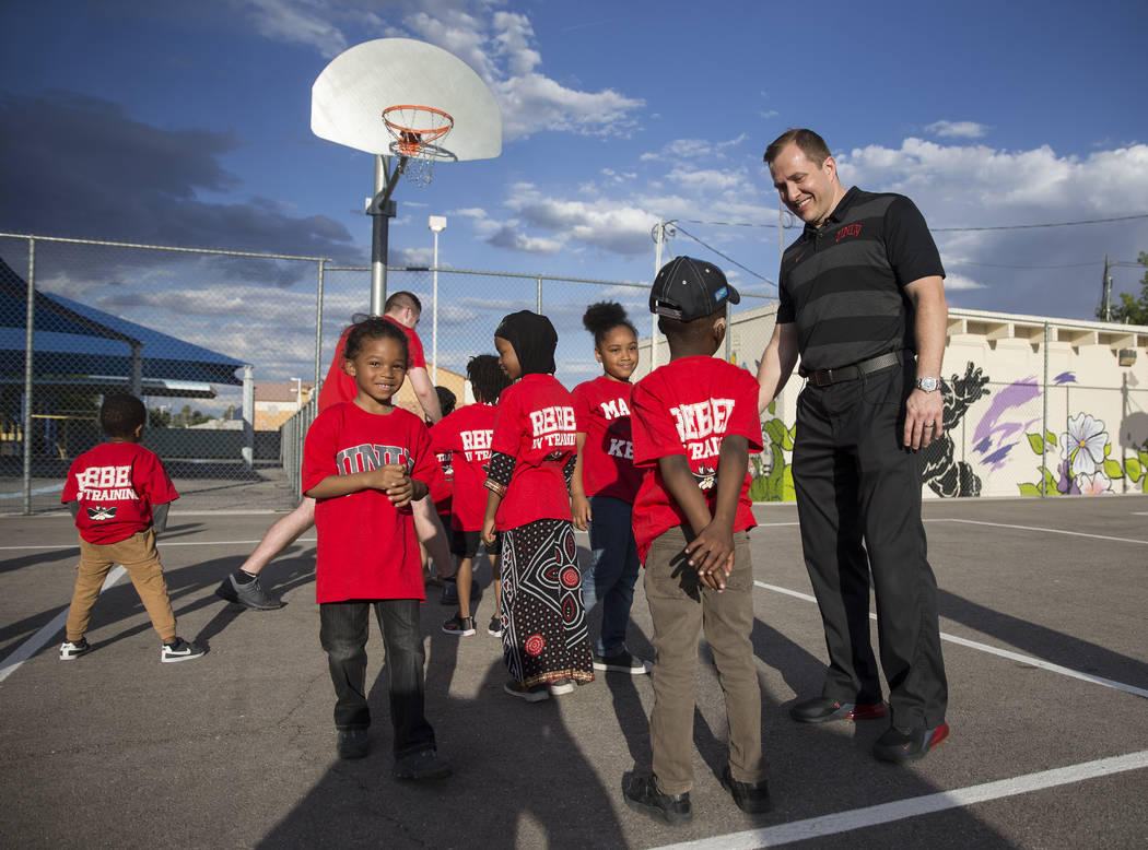 UNLV head basketball coach T.J. Otzelberger, right, talks with kids during a youth clinic at th ...