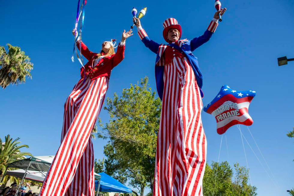Patriotic stilt walkers wave to crowds during the Summerlin Council Patriotic Parade in Summerl ...