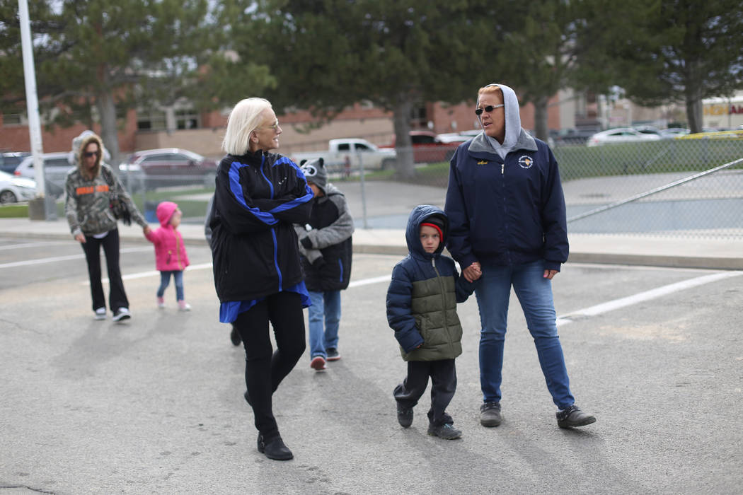 Jennifer Hood speaks to April Carlson and her grandson Bentley Brown, 4, as they walk to a park ...