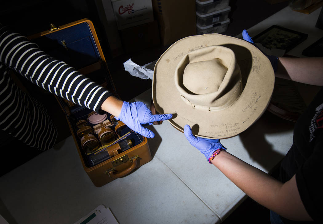 Doctoral student Paige Figanbaum, left, points to a cowboy hat with written markings referencin ...