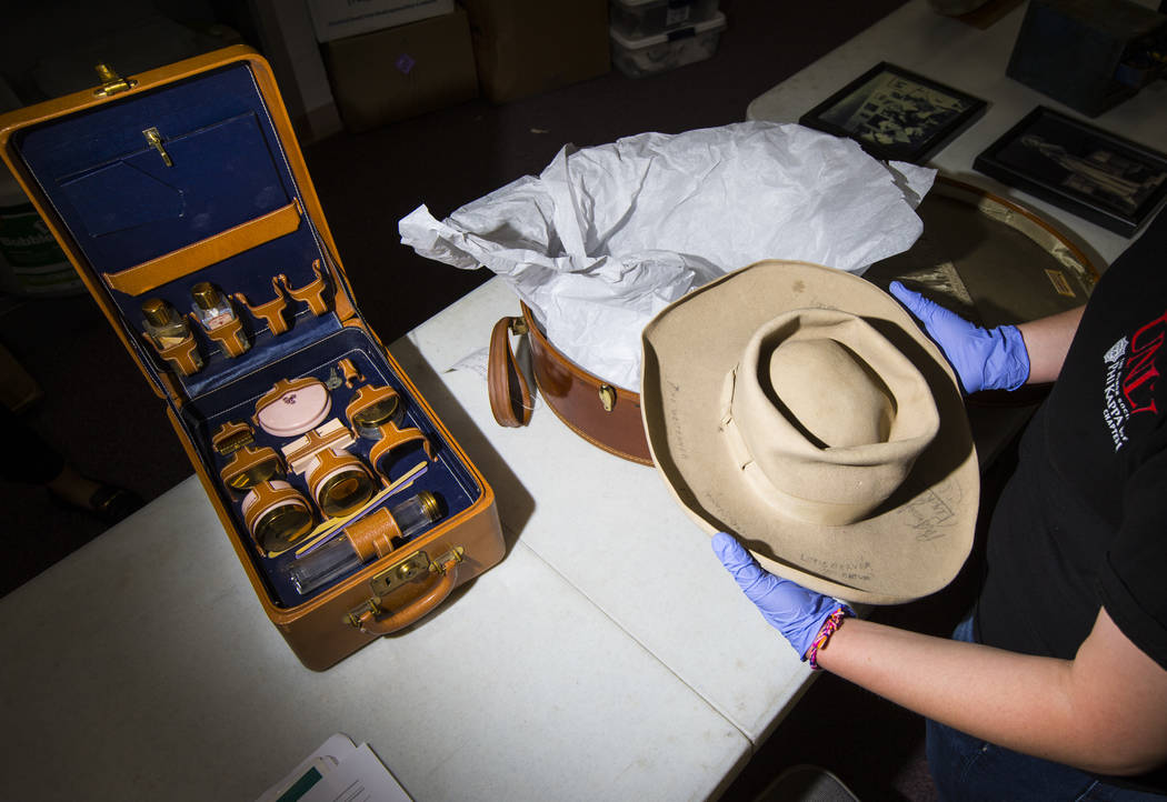Senior history student Kassidy Whetstone examines a cowboy hat with written markings referencin ...