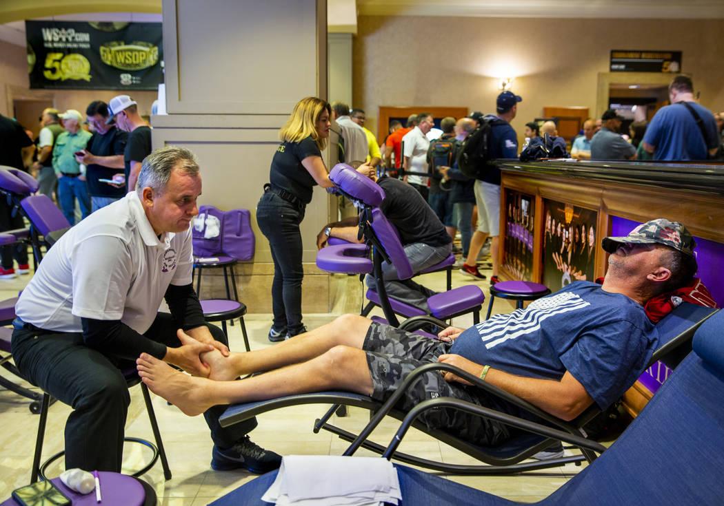 Mirek Rurka with Professional Massage Inc., works the feet of poker player Darren Hicks, of Cor ...