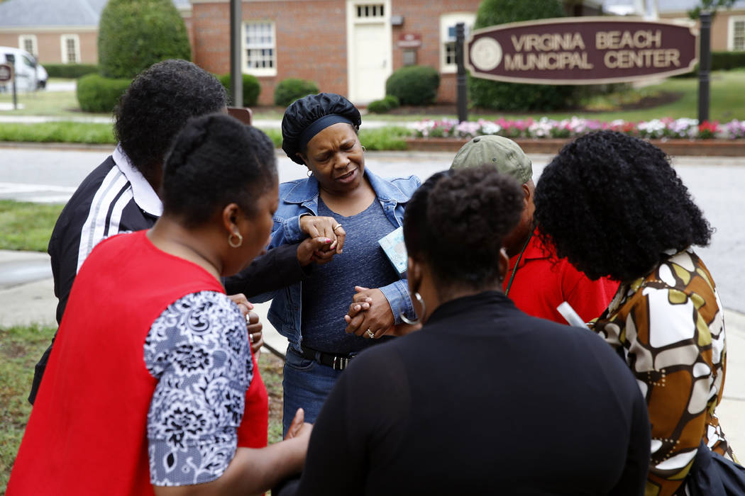 Members of Mount Olive Baptist Church pray near a municipal building that was the scene of a sh ...