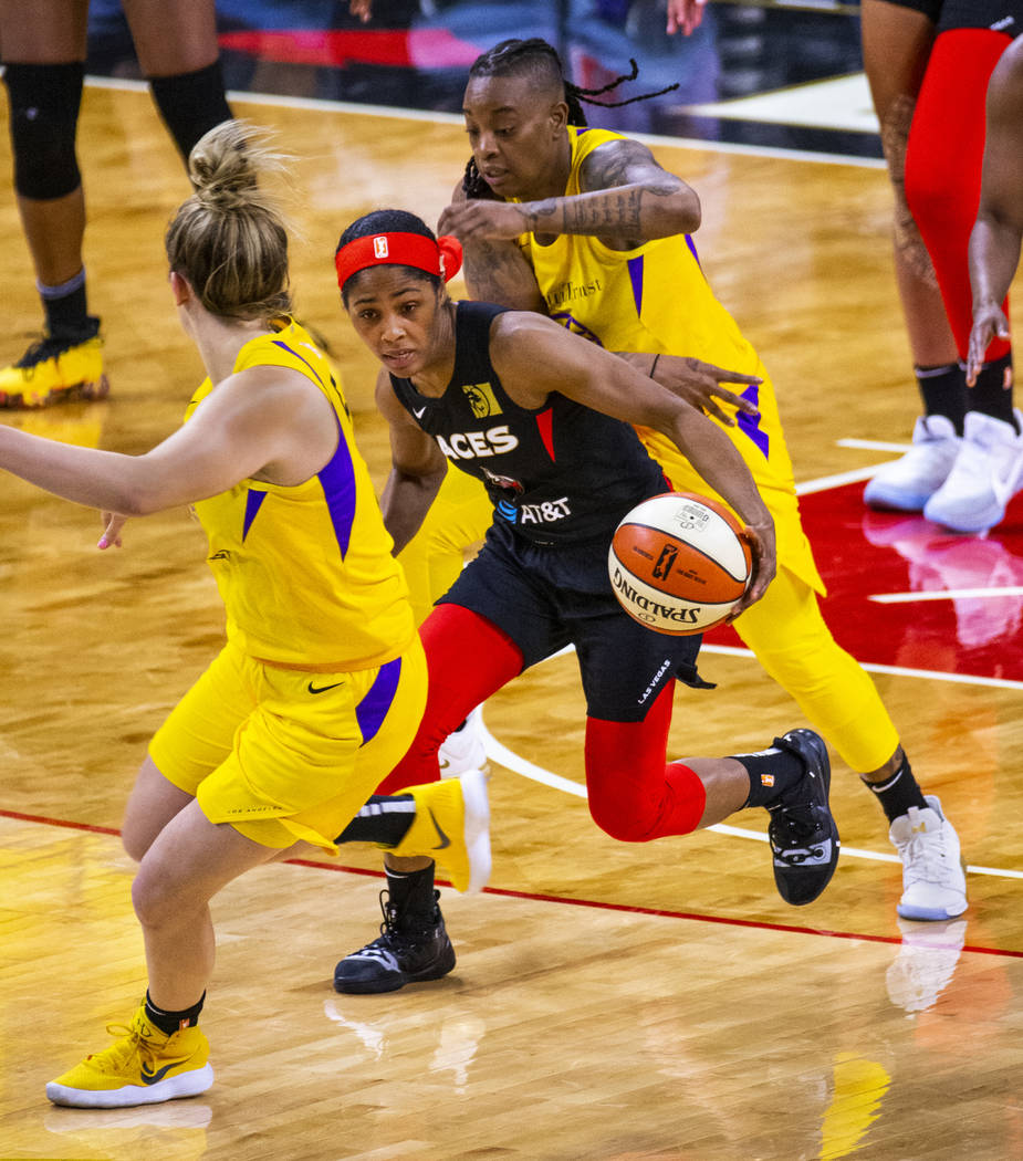 Las Vegas Aces guard Sydney Colson (51) drives the court between Los Angeles Sparks guard Marin ...