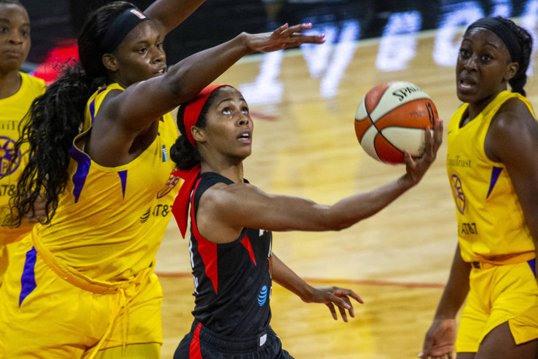 Las Vegas Aces guard Sydney Colson (51) gets off a reverse layup past Los Angeles Sparks center ...