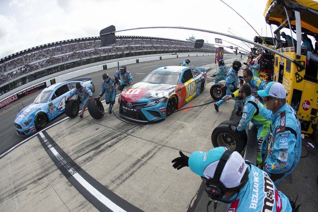 Kyle Busch (18) and Kevin Harvick (4) make pit stops during a NASCAR Cup Series auto race at Po ...