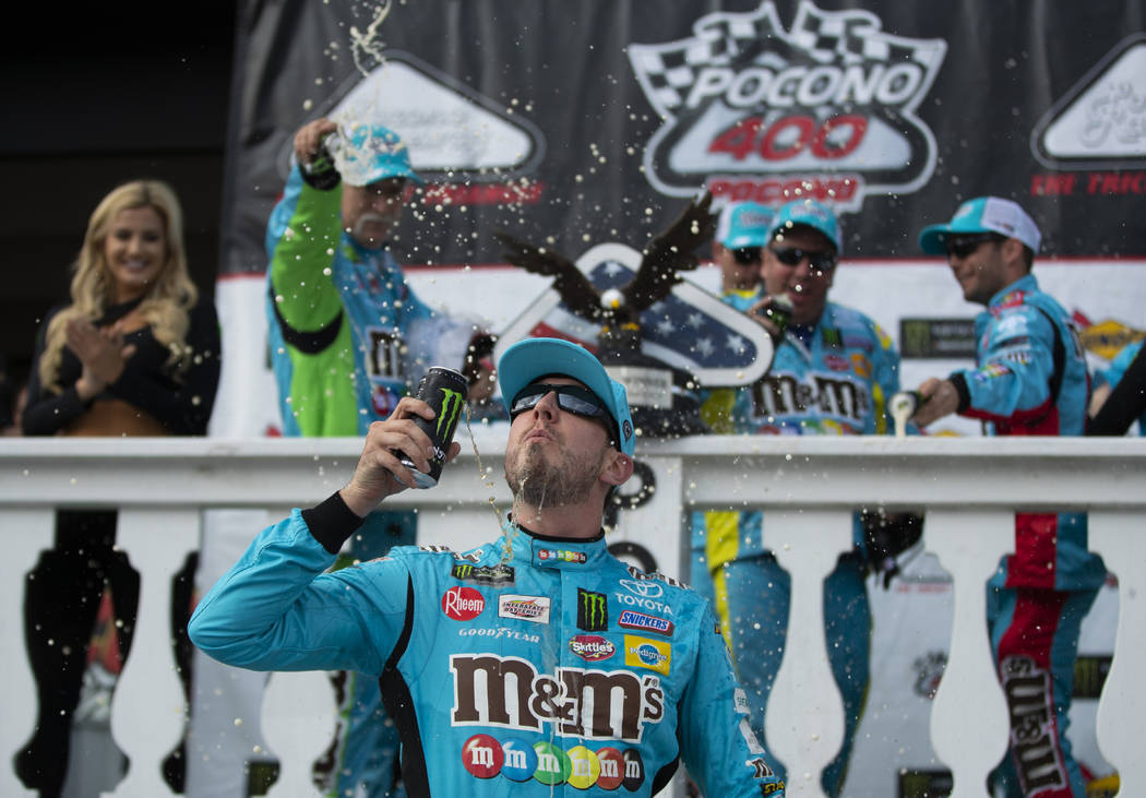 Kyle Busch celebrates in victory lane after winning a NASCAR Cup Series auto race at Pocono Rac ...