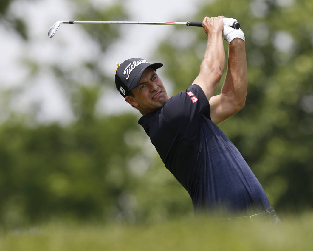 Adam Scott, of Australia, tees off on the third hole during the final round of the Memorial gol ...