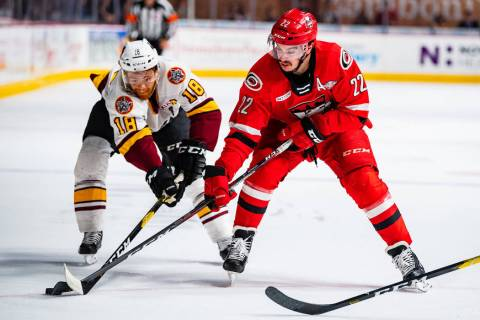 Chicago Wolves center T.J. Tynan (18) battles Charlotte Checkers right wing Andrew Poturalski f ...