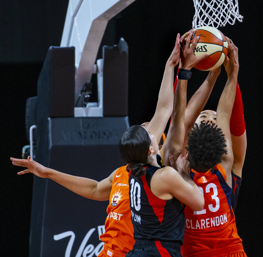 Las Vegas Aces guard Kelsey Plum (10) and teammate center Ji-Su Park (19) team up to take a reb ...