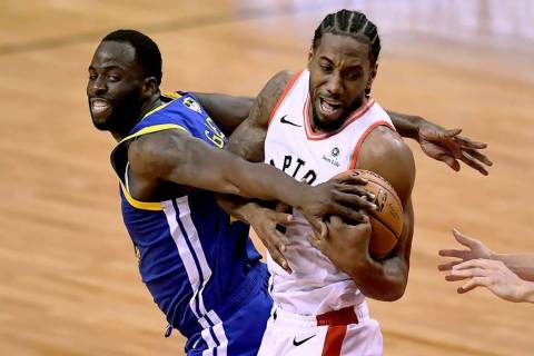 Golden State Warriors forward Draymond Green (23) tries to take the ball from Toronto Raptors f ...