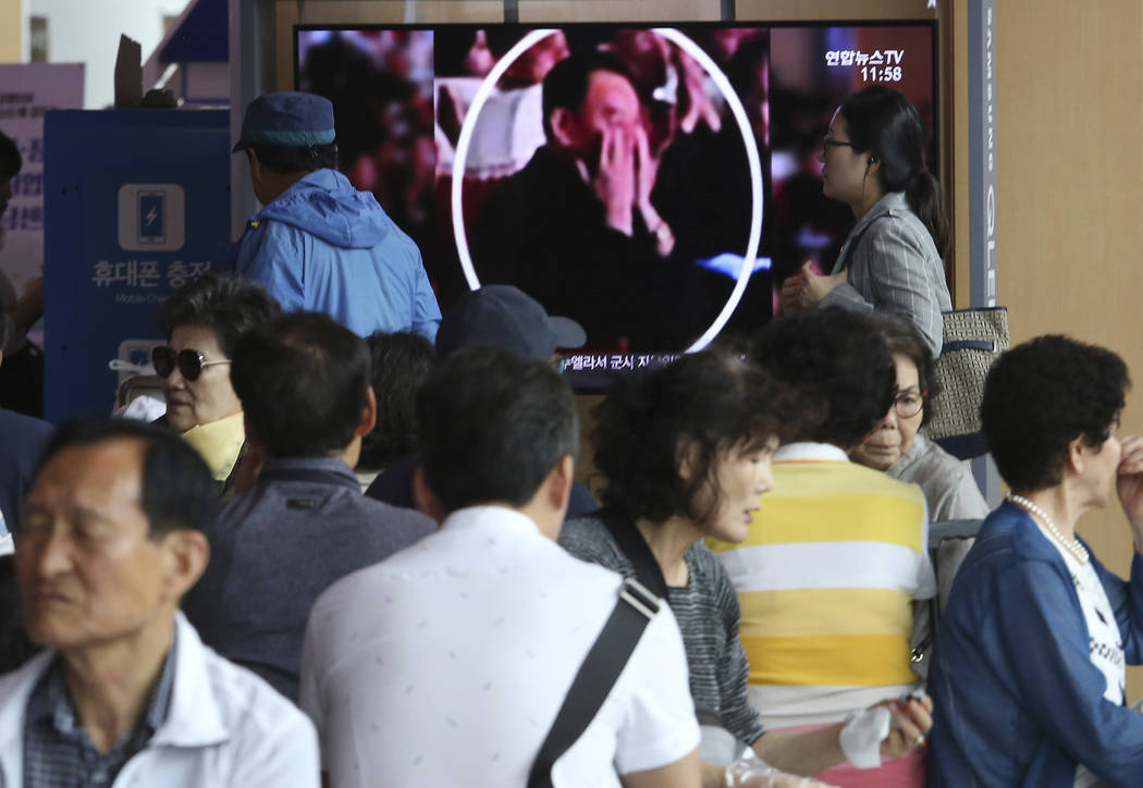 People watch a TV screen showing an image of senior North Korean official Kim Yong Chol in a mu ...