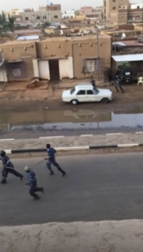 In this image made from video, Police officers running down a street in Khartoum, Sudan, on Mon ...