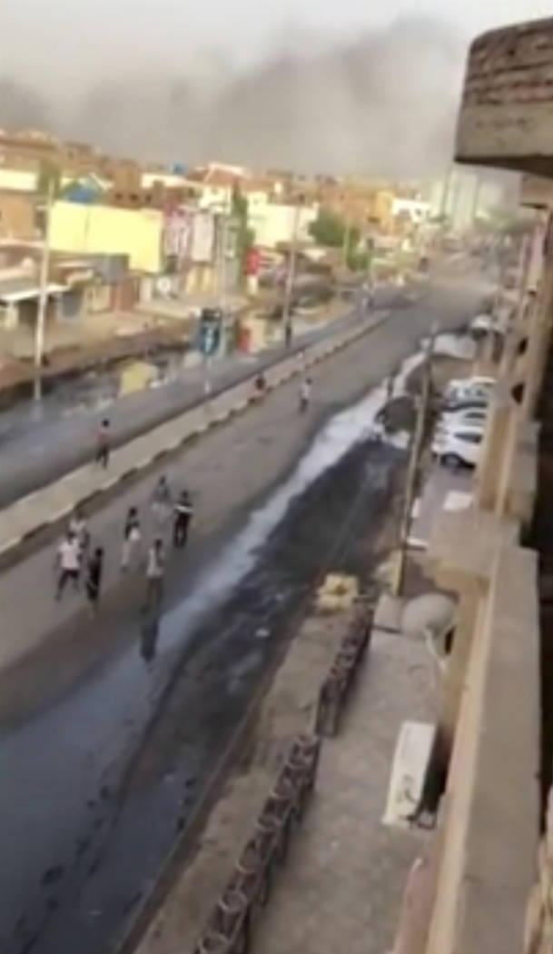 In this image made from video, civilians walk down a street in Khartoum, Sudan with plumes of s ...