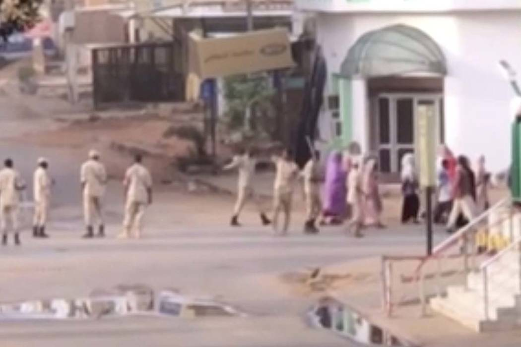 In this image made from video, Sudanese forces escort civilian in Khartoum, Sudan on Monday, Ju ...