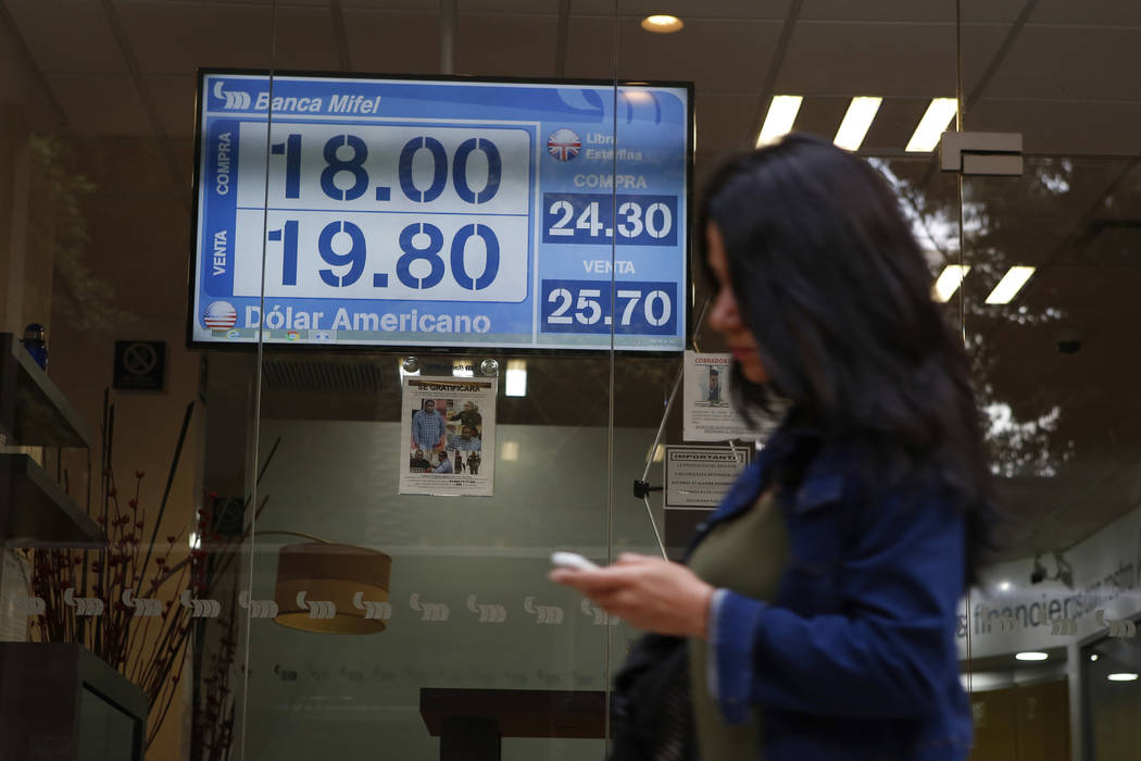 A sign displays exchange rates on a storefront window in Mexico City, Mexico, Friday, May 31, 2 ...