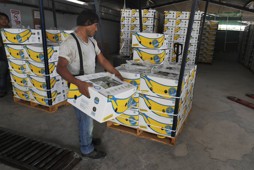 FILE - In this May 31, 2019 file photo, a worker stacks a box of freshly harvested Chiquita ban ...