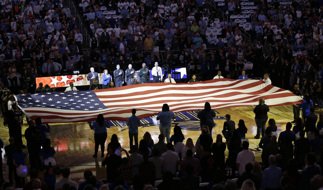 FILE - In this Wednesday, Oct. 26, 2016 file photo, first responders hold a flag on the court a ...