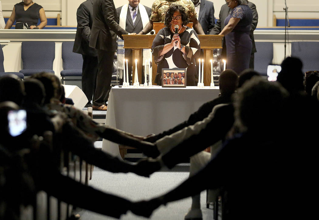 After lighting 12 candles, Veronica Coleman leads the congregation in prayer during a vigil for ...