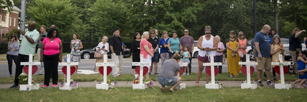 Community members stand by the 12 crosses at the memorial located by Building 11 of the Virgini ...