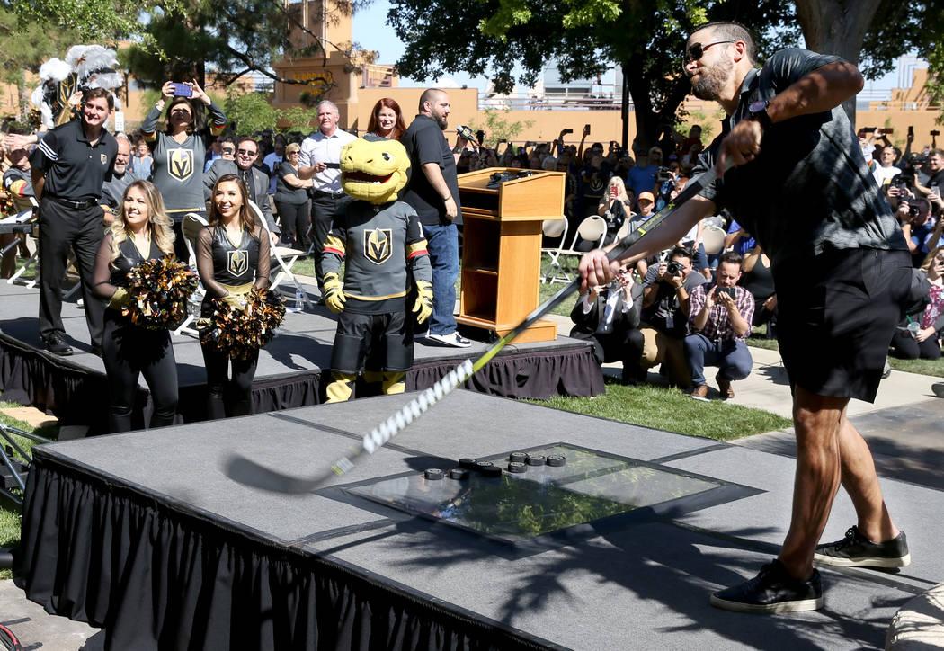 Vegas Golden Knights defenseman Deryk Engelland hits a puck through a ceremonial plate of glass ...