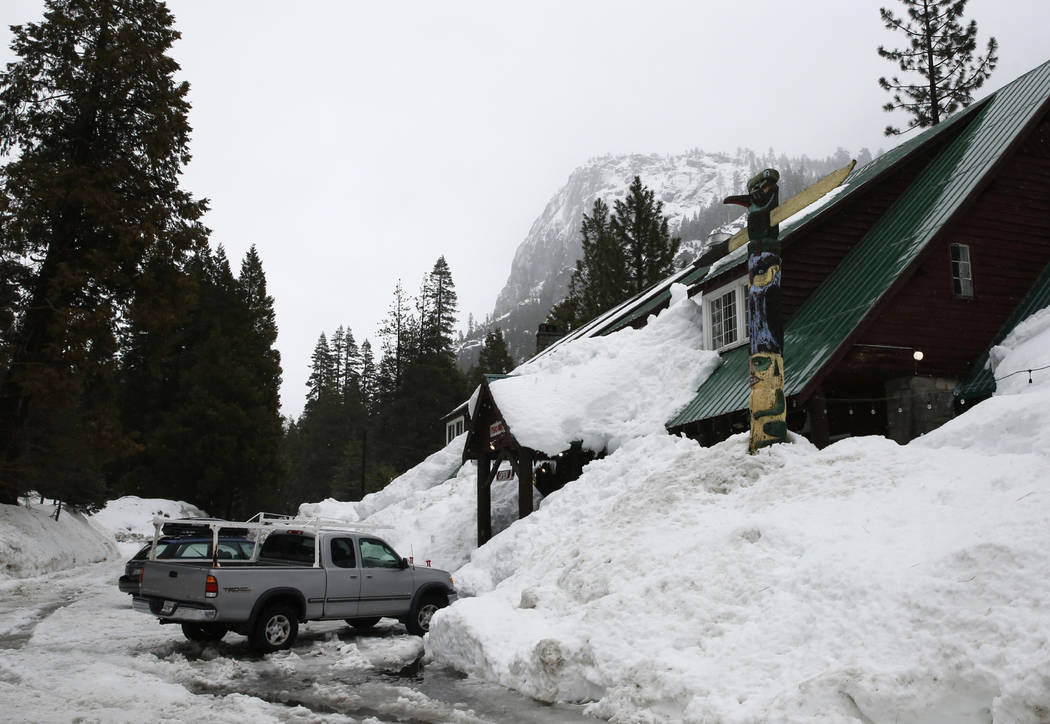 In this Feb. 28, 2019, file photo, snow, from storms is piled up as high as the eves of the Str ...