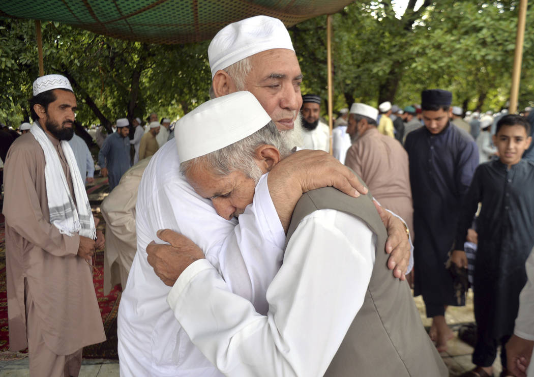 Pakistani Muslims greet each other after offering the Eid al-Fitr prayers, which marks the end ...