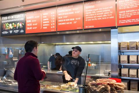 In this Dec. 15, 2015 file photo, a Chipotle Mexican Grill employee, right, prepares a burrito ...