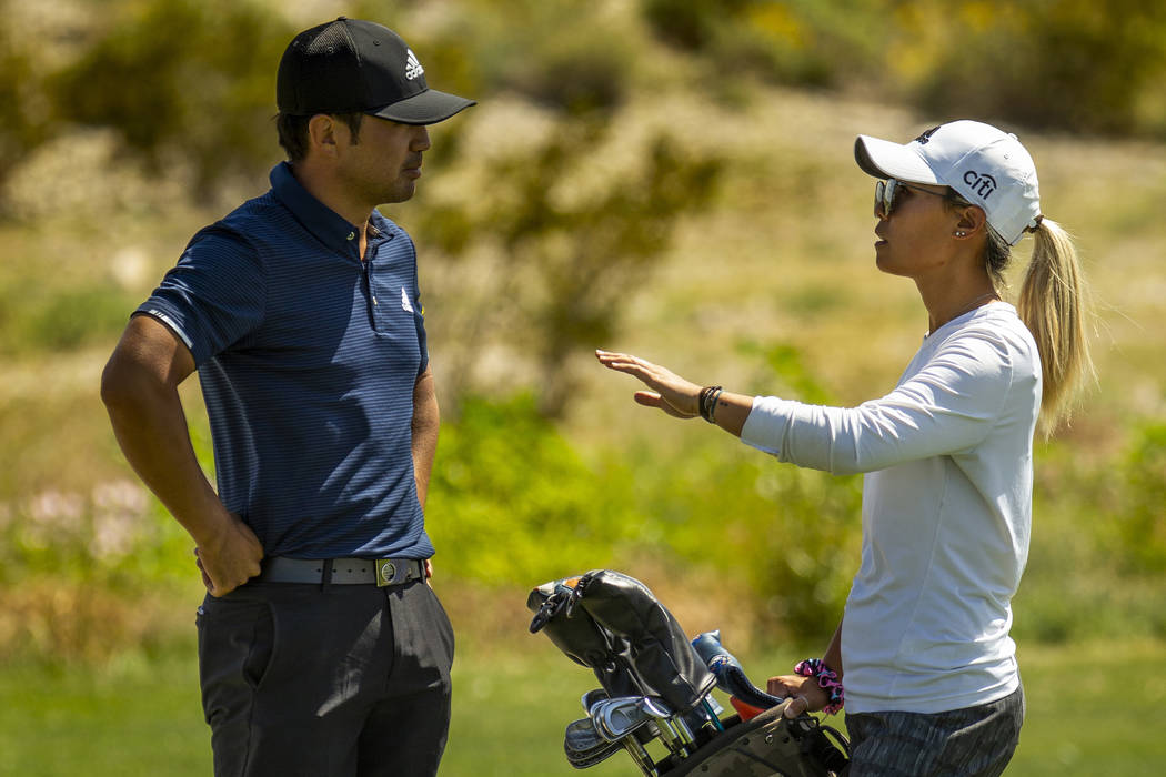Golfer Alexander Kang listens to his sister and caddy LPGA golfer Danielle Kang on the course d ...